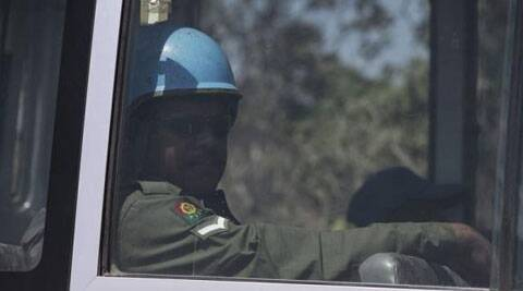 A U.N. peacekeeper from Fiji is seen through a bus window in the Israeli-occupied Golan Heights, before crossing into Syria. (Source: Reuters)