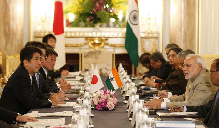 Narendra Modi, second right, and Japanese Prime Minister Shinzo Abe, left, talk during their meeting at the Akasaka State Guesthouse in Tokyo Monday. <br /> Modi who was on his official visit to Japan, courted Japan's government and business leaders Monday, winning pledges of help for his effort to revitalize the lagging Indian economy. (Source: PTI)