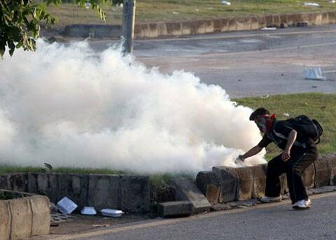 A Pakistani protester picks up a tear gas canister to throw back towards police during a clash in Islamabad. (Source: AP)