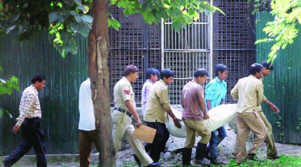 Zoo officials carry Maqsood's body away from the enclosure. (Source: Express photo by Oinam Anand)