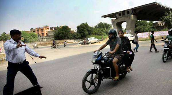 Traffic police runs to catch a woman without helmet on bike in New Delhi on Wednesday. (Source: Express photo by Praveen Khanna)