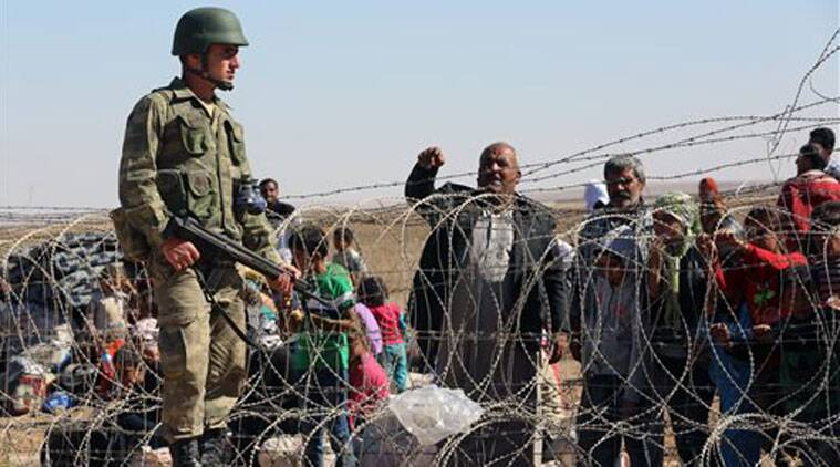 A Turkish soldier stands guard as several hundred Syrian refugees wait to cross the border in Suruc, Turkey, Sunday. (Source: AP)