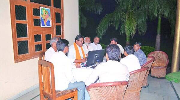 Tyagi, wearing the saffron stole, with a group of RSS volunteers at his home cum 'headquarters'. (Source: Express photo)