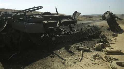 A column of destroyed Ukrainian military vehicles are abandoned near a village; Andrei Stenin's car was hit by shots and burnt on the road close to Donetsk during the rebel stronghold in Eastern Ukraine. ( Source: AP )