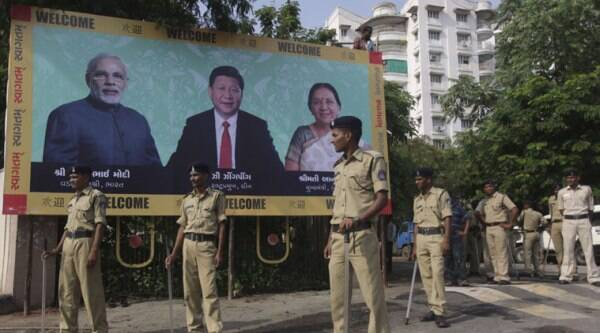 Indian policemen stand next to a welcome hoarding being erected ahead of an anticipated visit by Chinese President Xi Jinping as they review security arrangements in Ahmadabad, India, Monday, Sept. 15, 2014. (Source: AP)