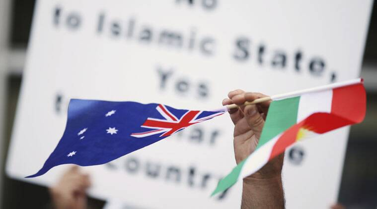A man holds up the Australian and Kurdistan flags as members of Australian Kurdish Community gather in central Sydney against ISIS.