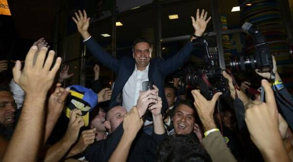 Aecio Neves, presidential candidate of the Brazilian Social Democracy Party, PSDB, center, celebrates with supporters after a press conference in Belo Horizonte, Brazil, Sunday, Oct. 5, 2014. (Source: AP)