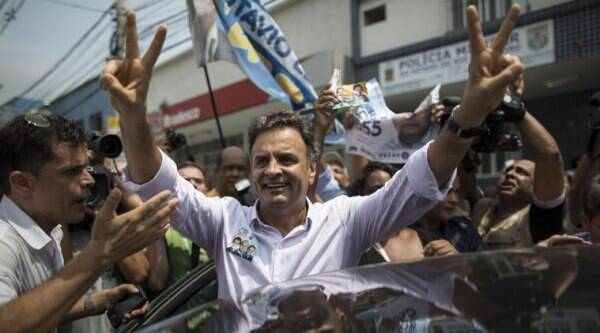 """FILE - In this Sept. 30, 2014 file photo, Aecio Neves, presidential candidate of the Brazilian Social Democracy Party, PSDB, flashes a victory sign as he campaigns at the """"Mercadao de Madureira,"""" or Madureira Market in Rio de Janeiro, Brazil. Brazil will hold general elections on Oct. 5. (Source: AP)"""