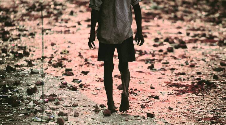 BRICK LANE: A Trilokpuri boy walks over broken bricks and shards of glass, remains of Saturday's rioting.(Express photo by Oinam Anand)