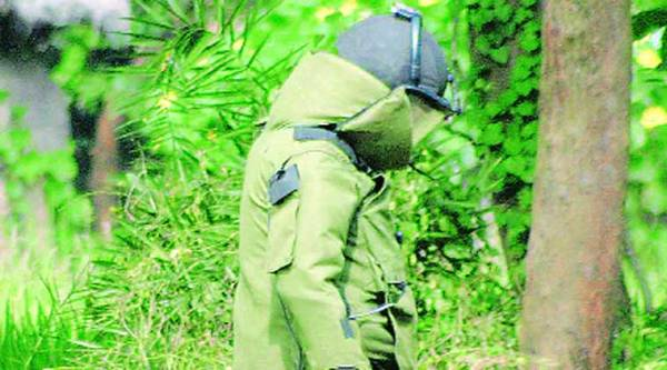 A bomb squad personnel of CID defuses crude bombs recovered from a primary health centre at Sattore in Birbhum district of West Bengal on Saturday. (Express)