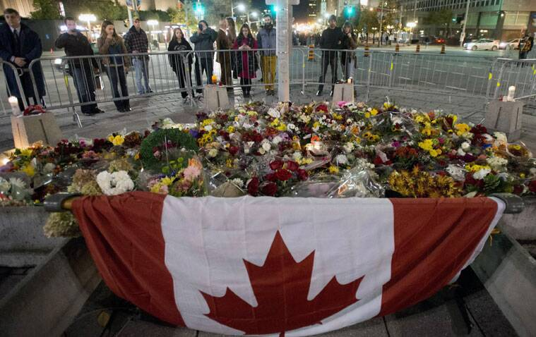 People look at the makeshift memorial near the National War Memorial near Parliament Hill, where Cpl. Nathan Cirillo, 24, was killed by a gunman. (Source: AP)