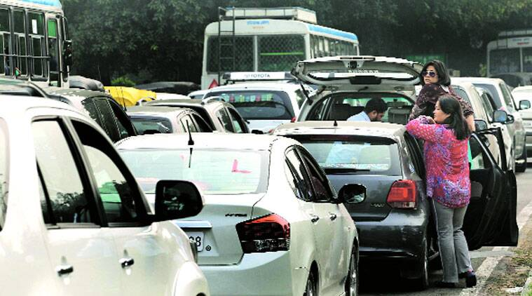 People wait during the traffic jam while the convoy of Prime Minister Narendra Modi crosses the Industrial Area roundabout in Chandigarh on Sunday. (Source: Express photo by Kamleshwar Singh)