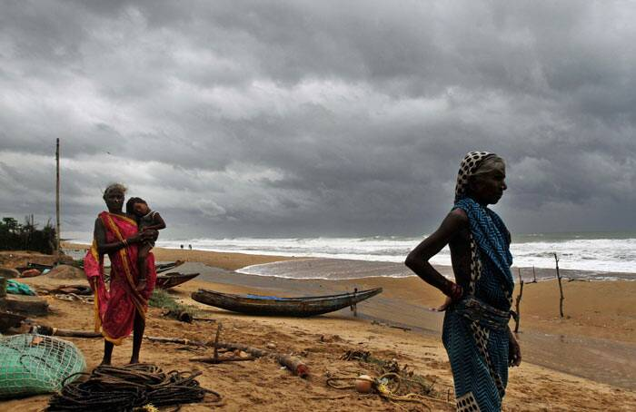 """Fisherwomen watch the sea waves before evacuating the place near Podampeta village, on the outskirts of Gopalpur beach in Ganjam district, 140 kilometers (87 miles) south of Bhubaneswar, India, Saturday, Oct. 11, 2014. Indian authorities were evacuating hundreds of thousands of people Saturday as a powerful cyclone """"Hudhud"""" swept through the Bay of Bengal and headed toward the country's east coast. (Source: AP)"""