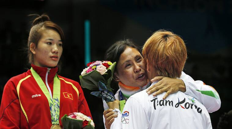 Sarita hugs her South Korean counterpart at the podium. (Source: AP)