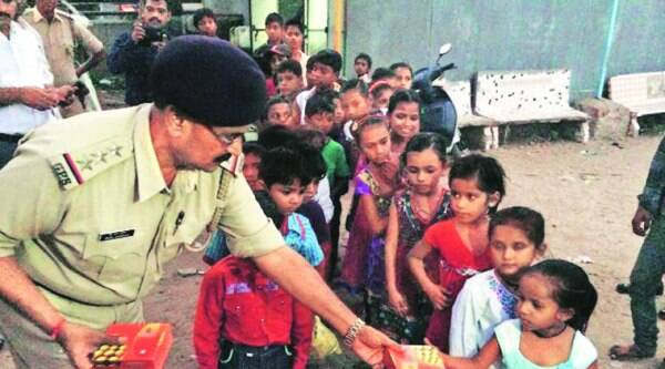 A police official distributes sweets to children living in slums, in Ahmedabad on Wednesday. (Source: IE photo by Javed Raja)