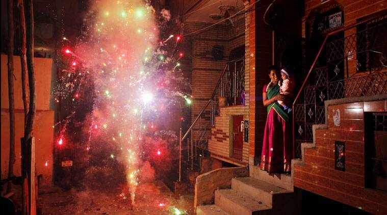An Indian woman holds her child and watches a firecracker light up during Diwali, the festival of lights, in New Delhi. (Source: PTI)