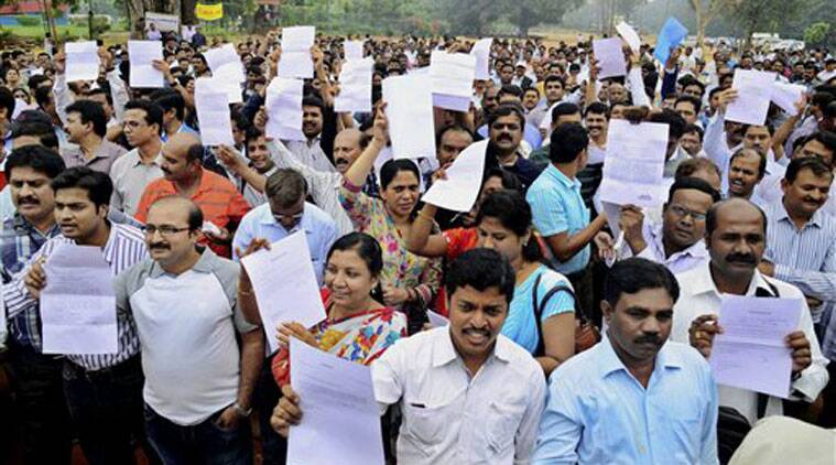 Doctors, working in government hospitals, showing their resignation letters during a protest at freedom park in Bengaluru on Monday. (Source: PTI)