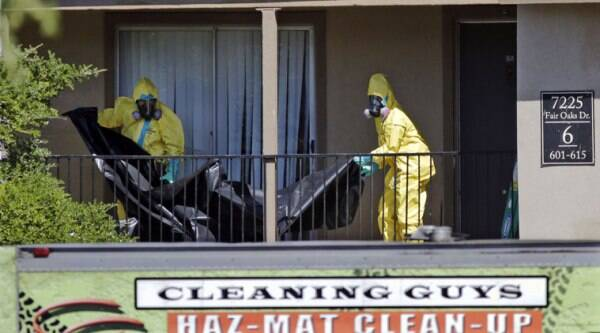 File - In the Oct. 3, 2014 file photo, hazardous material cleaners prepare to hang black plastic outside The Ivy Apartments in Dallas. A 15-member crew from the Cleaning Guys of Fort Worth labored for four days at the apartment where Thomas Eric Duncan stayed when he began showing Ebola-related symptoms such as vomiting and diarrhea. (Source: AP)