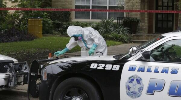 A hazmat worker cleans outside the apartment building of a hospital worker, Sunday, Oct. 12, 2014, in Dallas. (Source: AP)