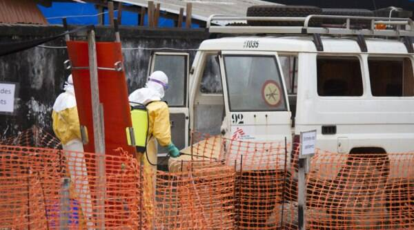Health workers spray a vehicle, used for collecting bodies, with disinfectant at an Ebola Isolation centre run by Doctors Without Borders in Donka, Guinea. (Source: AP photo)