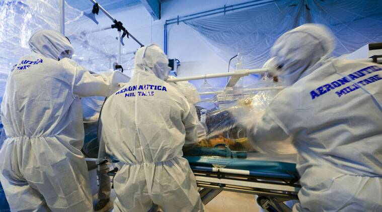 Participants into a course to learn how to transport and handle contagious patients use an 'Aircraft Transit Isolator' to carry a colleague during a simulation at the military airport of Pratica di Mare, Rome. (AP Photo)