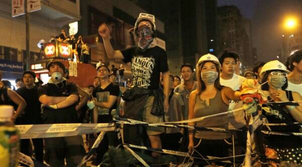 A student protester rests next to a defaced cut-out of Hong Kong's Chief Executive Leung Chun-ying at one of their protest sites around the government headquarters, Tuesday, Sept. 30, 2014, in Hong Kong. (source: AP)