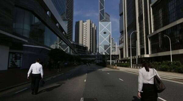 People walk to work on a main road to the Central, in Hong Kong, Monday, Oct. 6, 2014. Hong Kong's civil servants returned to work and schools were reopening Monday as a massive pro-democracy protest that has occupied much of the city center for the week dwindled. (Source: AP)