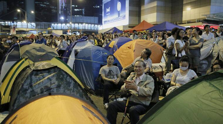 Pro-democracy protesters cheer as they listen to student leader's speeches after talks between Hong Kong government officials and students at an occupied area outside the government headquarters in Hong Kong's Admiralty district,Tuesday, Oct. 21, 2014. (Source: AP)