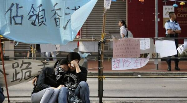 Protesters rest after police removed barricades that protesters set up to block off main roads in Causeway Bay district in Hong Kong Tuesday, Oct. 14, 2014. (Source: AP)