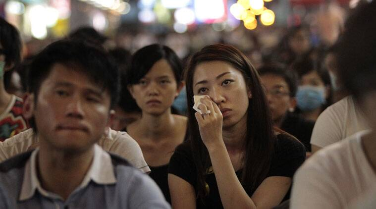 A pro-democracy student protester wipes her eyes as she watches with others a live broadcast of government officials meeting with student protest organizers, in the Mong Kok district of Hong Kong, Tuesday, Oct. 21, 2014.  (Source: AP)