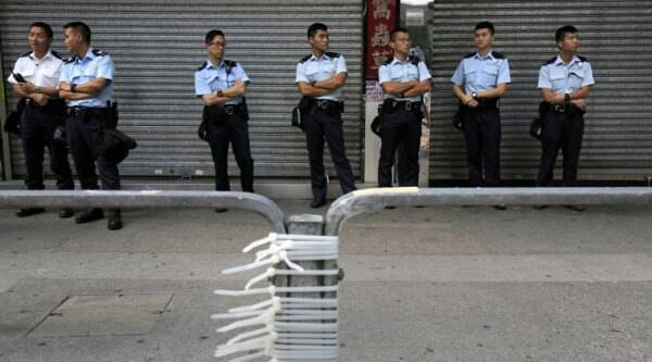 Police officers stand guard after removing barricades that protesters have set up to block off main roads in Causeway Bay district in Hong Kong Tuesday, Oct. 14, 2014. Hong Kong police removed some of the barricades in a shopping district and opened one road that had been blocked by pro-democracy protesters for more than two weeks. (Source: AP)