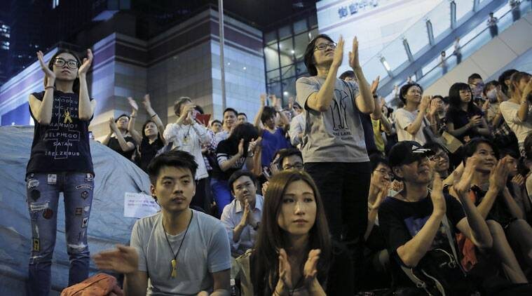 Pro-democracy protesters cheer as they listen to student leader after talks between Hong Kong government officials and students at an occupied area outside the government headquarters in Hong Kong's Admiralty district,Tuesday, Oct. 21, 2014. (Source: AP)