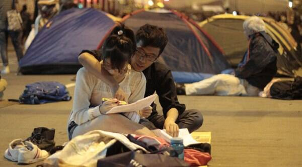 Pro-democracy students work on their homework at their occupied intersection in the Mong Kok district of Hong Kong, Thursday, Oct. 16, 2014. (Source: AP)