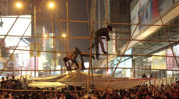 Supporters of the pro-democracy student protest construct bamboo barricades at an occupied intersection in the Mong Kok district of Hong Kong, Wednesday, Oct. 15, 2014. (Source: AP)