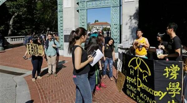 University of California at Berkeley students pass out yellow ribbons and educate others in support for the Umbrella Revolution, a group seeking democracy in Hong Kong (Source: AP)