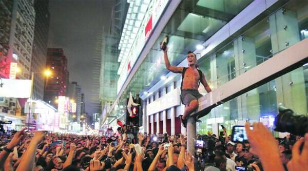 A pro-democracy student protester scales a traffic light pole in defiance to local residents in Mong Kok Friday night. (Source: AP)