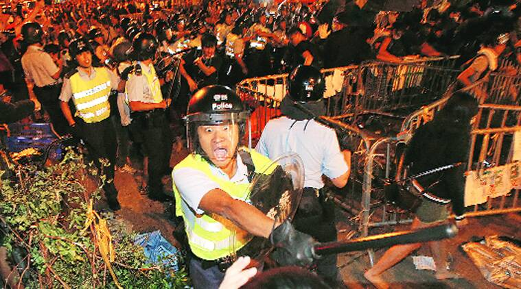 A riot police officer swings his baton at a protester in Mong Kok district of Hong Kong. Source: AP