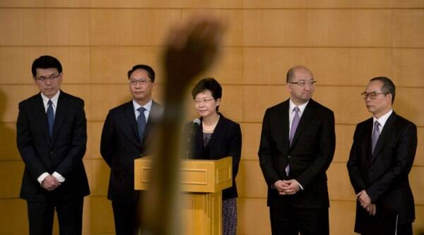 A reporter raises a hand to cast a question as Hong Kong government officials, from right, Undersecretary of the Constitutional and Mainland Affairs Bureau Lau Kong-wah, Secretary for Constitutional and Mainland Affairs Raymond Tam, Chief Secretary for Administration Carrie Lam, Secretary for Justice Rimsky Yuen and Chief Executive's Office Director Edward Yau Tang-wah attend a news conference after their talks on constitutional development with the student leaders in Hong Kong Tuesday, Oct. 21, 2014. (Source: AP)