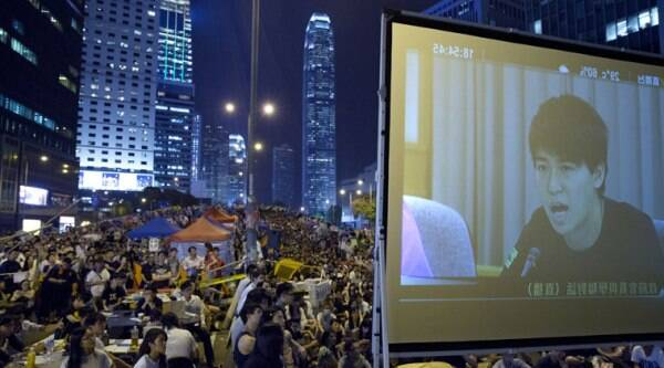 Pro-democracy protesters watch a live TV showing talks between Hong Kong government officials and students at an occupied area outside the government headquarters in Hong Kong's Admiralty district,Tuesday, Oct. 21, 2014. (Source: AP)