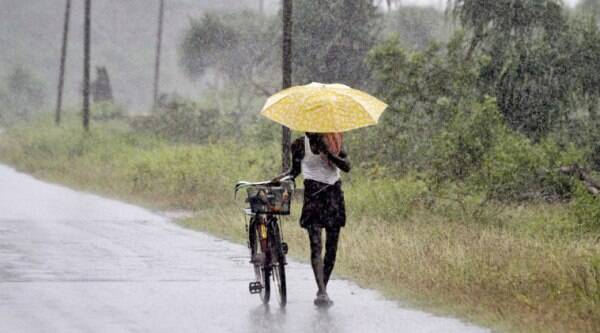 An Indian man holds an umbrella to protect himself from the heavy rains near Gopalpur, in Ganjam district, 140 kilometers (87 miles) south of Bhubaneswar, India, Saturday, Oct. 11, 2014. (Source: AP)