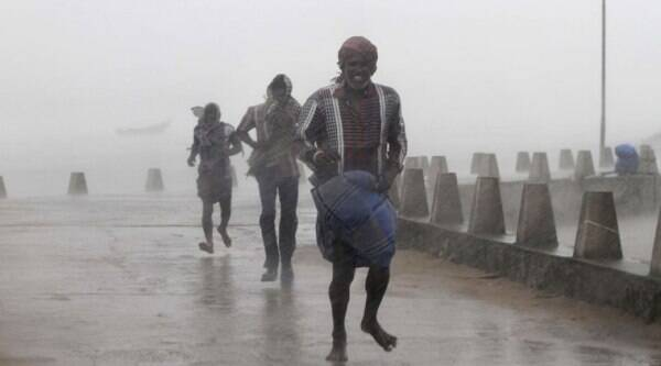 People run for shelter as heavy rain and wind gusts rip through the Bay of Bengal coast at Gopalpur, Orissa, about 285 kilometers (178 miles) north east of Visakhapatnam, India, Sunday, Oct. 12, 2014. (Source: AP)