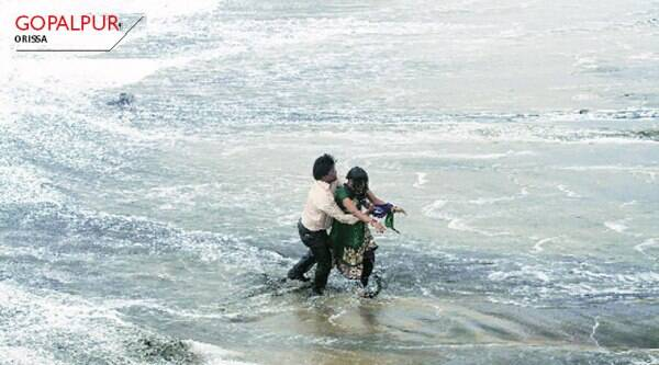 facing fury:  A man rescues a woman who fell in water due to strong tidal waves before the cyclone on Sunday; waves hit the beach as cyclone Hudhud makes landfall in Visakhapatnam on Sunday;  a house damaged by the cyclone.