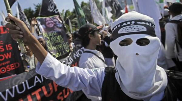 In this June 18, 2014 photo, a Muslim man wears a headband showing the Islamic State group's symbol during a protest calling for the closure of a local prostitution complex in Surabaya, Indonesia. (Source: AP)
