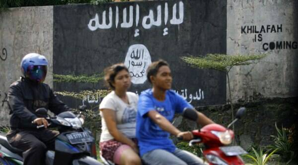In this March 8, 2014 photo, motorists ride past a graffiti of the Islamic State group's flag in Solo, Central Java, Indonesia. (Source: AP)