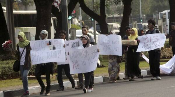 In this Sept. 5, 2014 photo, protesters walk with posters during a rally against the Islamic State group in Jakarta, Indonesia. (Source: AP)