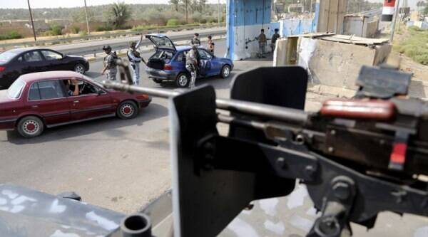 Iraqi federal policemen search a car at a checkpoint in Baghdad, Iraq, Saturday, Oct. 11, 2014. (Source: AP)