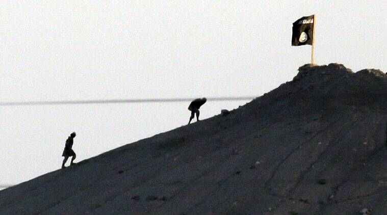 In this Oct. 6, 2014 file photo, militants with the Islamic State group are seen after placing their group's flag on a hilltop at the eastern side of the town of Kobani, Syria. (AP Photo)