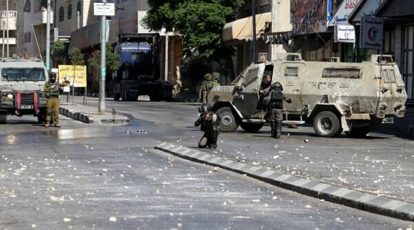Israeli soldiers and border policemen aim towards Palestinian protesters during clashes that erupted after Israeli troops shot dead two Palestinians, Amer Abu Aisheh and Marwan Qawasmeh in the West Bank city of Hebron, Tuesday, Sept. 23, 2014. (Source: AP)