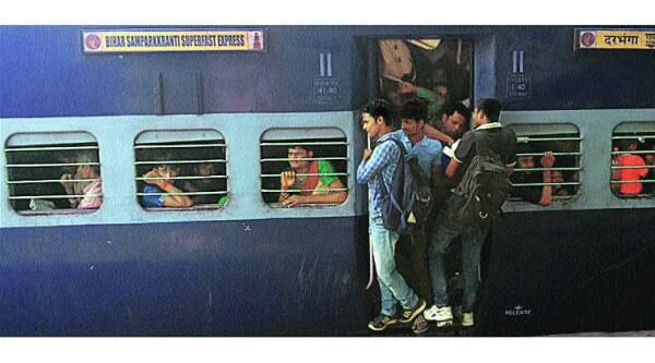 People travel on the footboard of a train bound for Bihar on Monday. ( Source: Express photo by: Praveen Khanna)