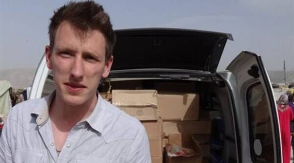 This undated photo provided by Kassig Family shows Peter Kassig standing in front of a truck filled with supplies for Syrian refugees. (Source: AP)